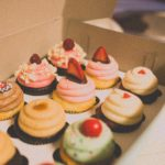 An assortment of specialty cupcakes in a box.