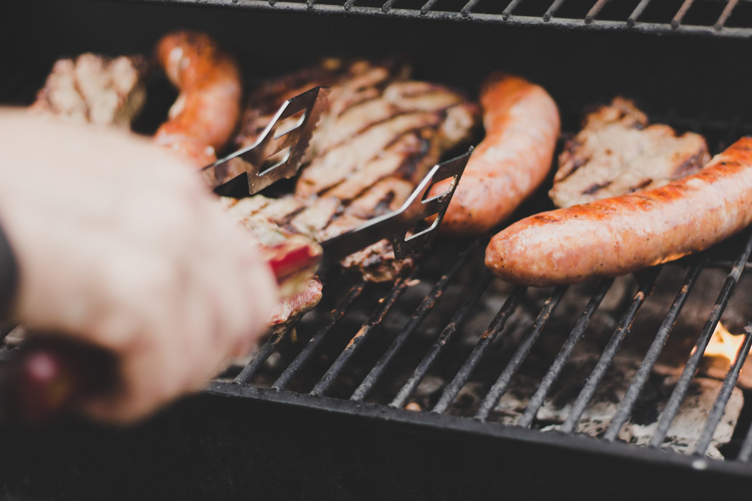 A person grilling sausage and other meat on a grill.