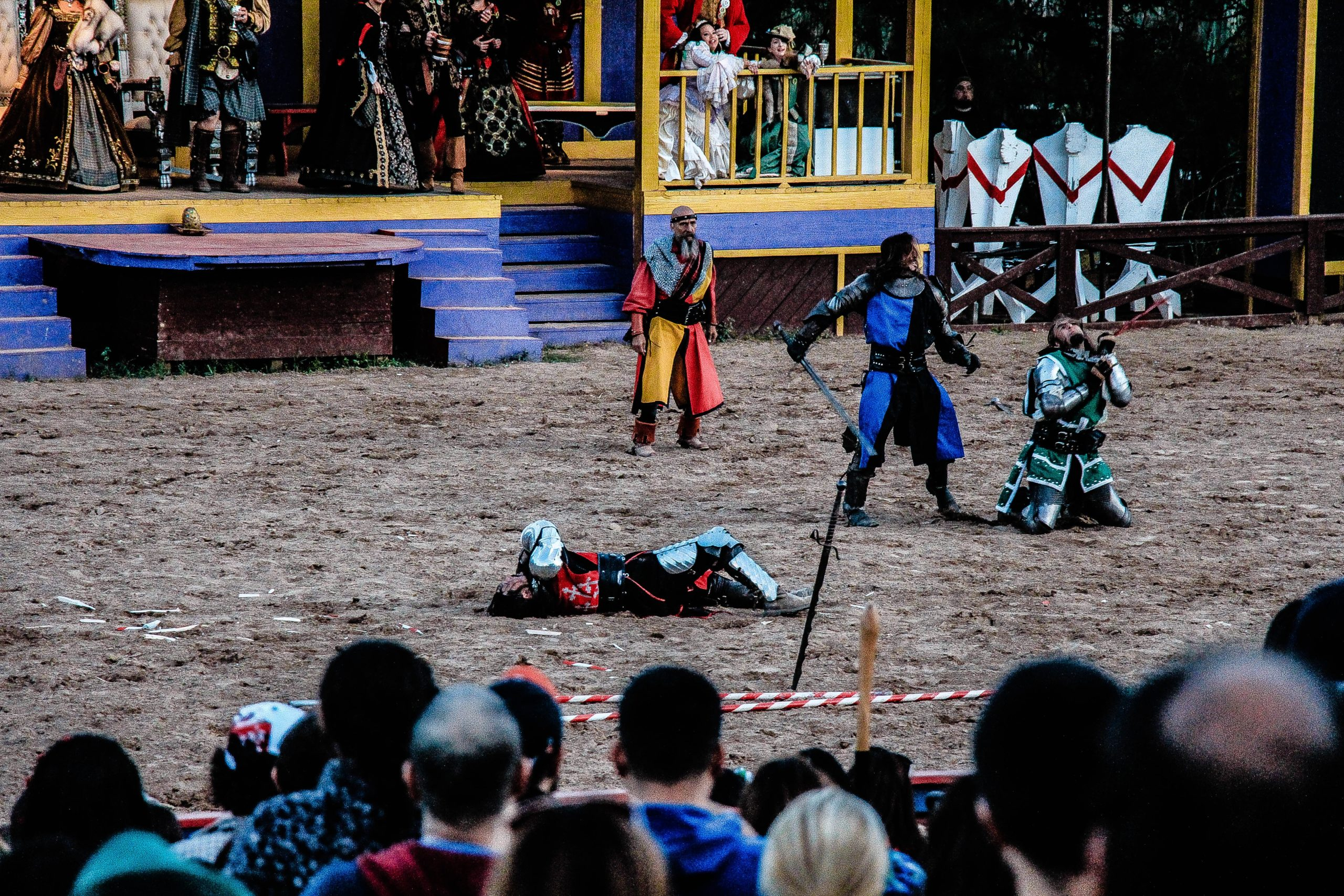 Knights fighting on the stage of a dinner theater while the audience watches.