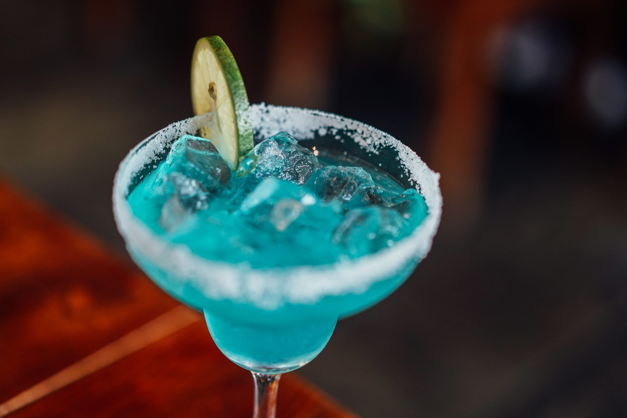 A blue margarita with a lime wedge and salt on the rim.