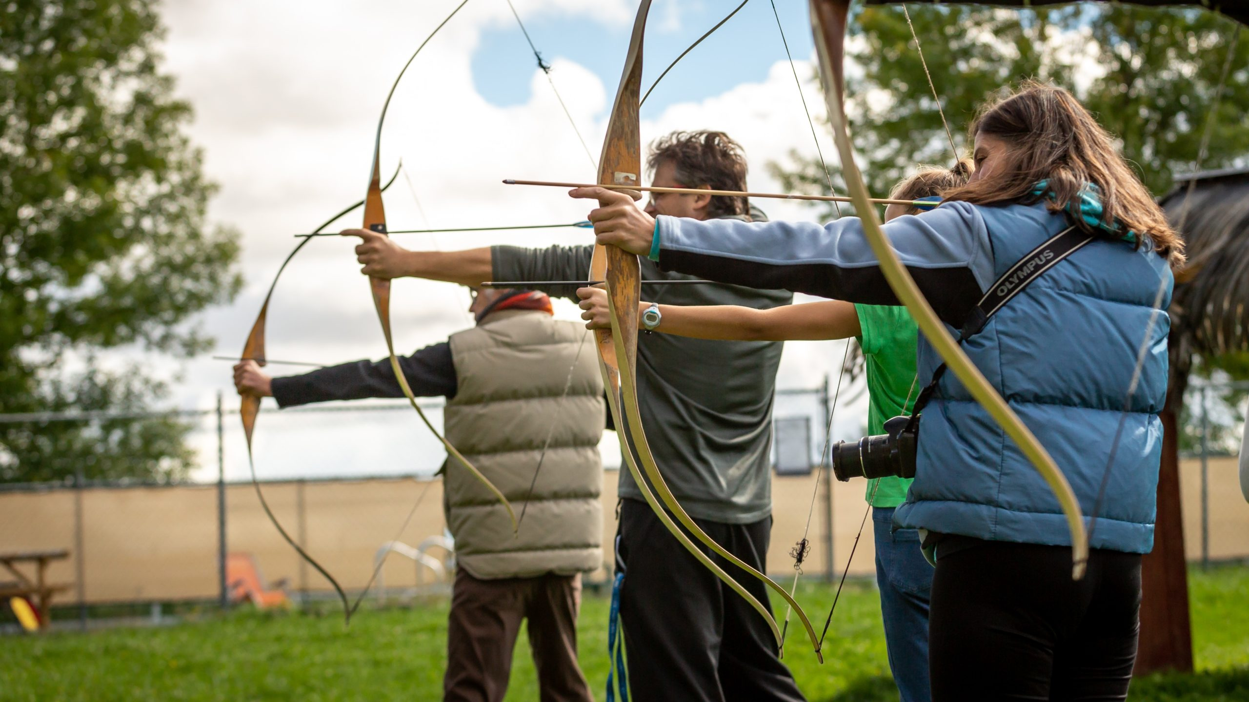 Three people practicing archery at an outdoor archery range.