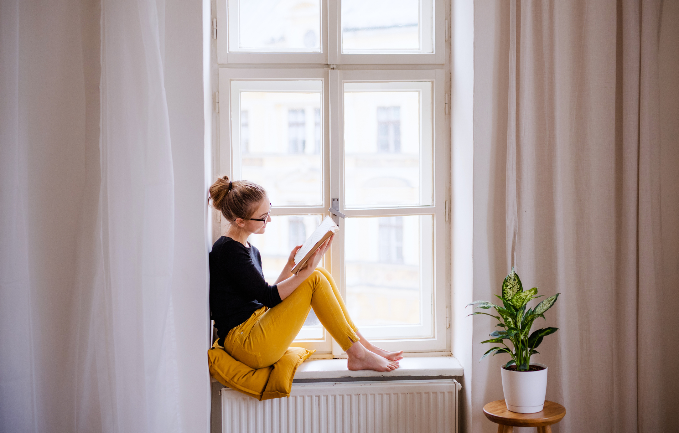 A girl reading a book inside her apartment.