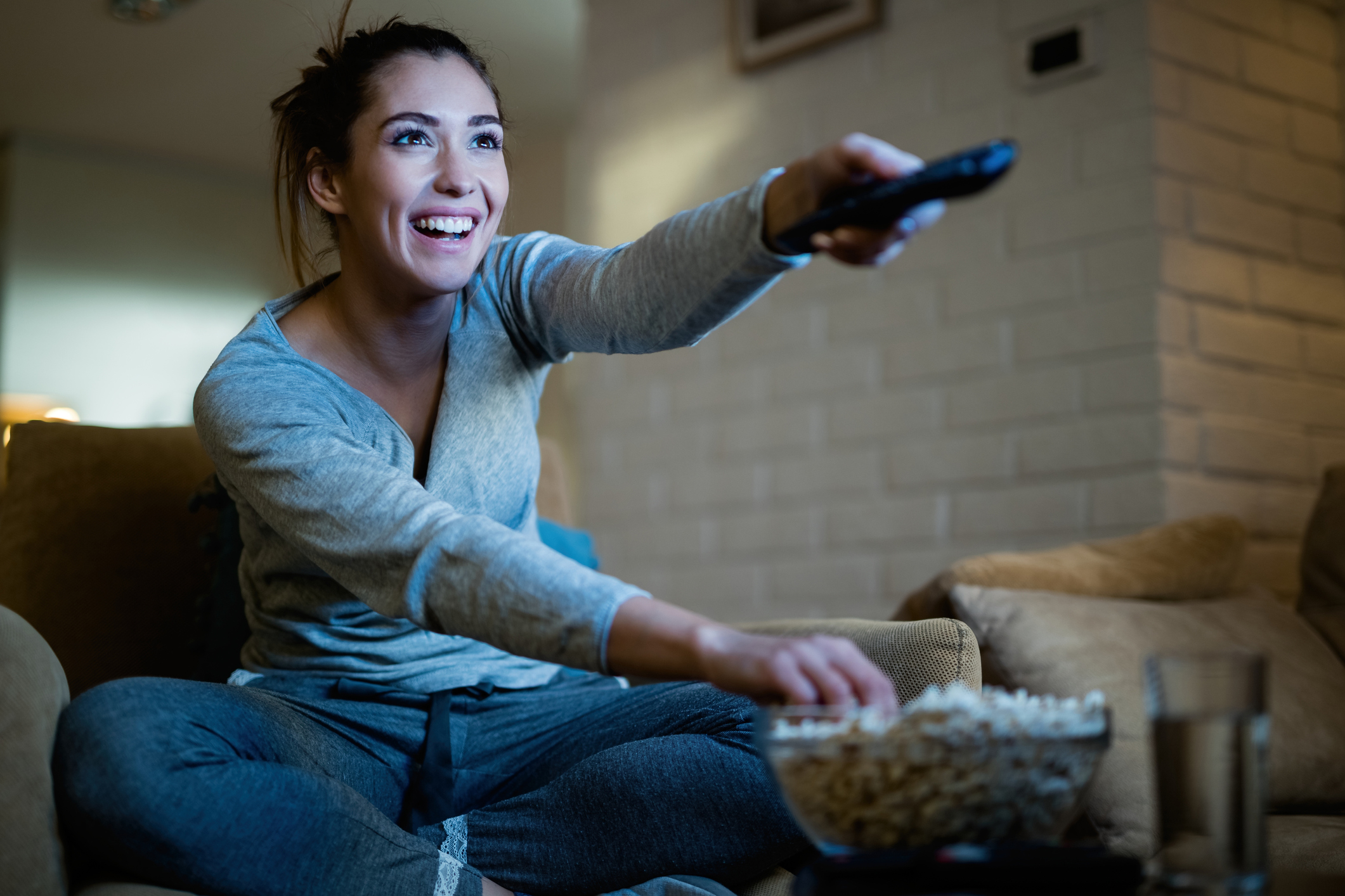A woman pointing the remote at her TV while reaching for some popcorn.