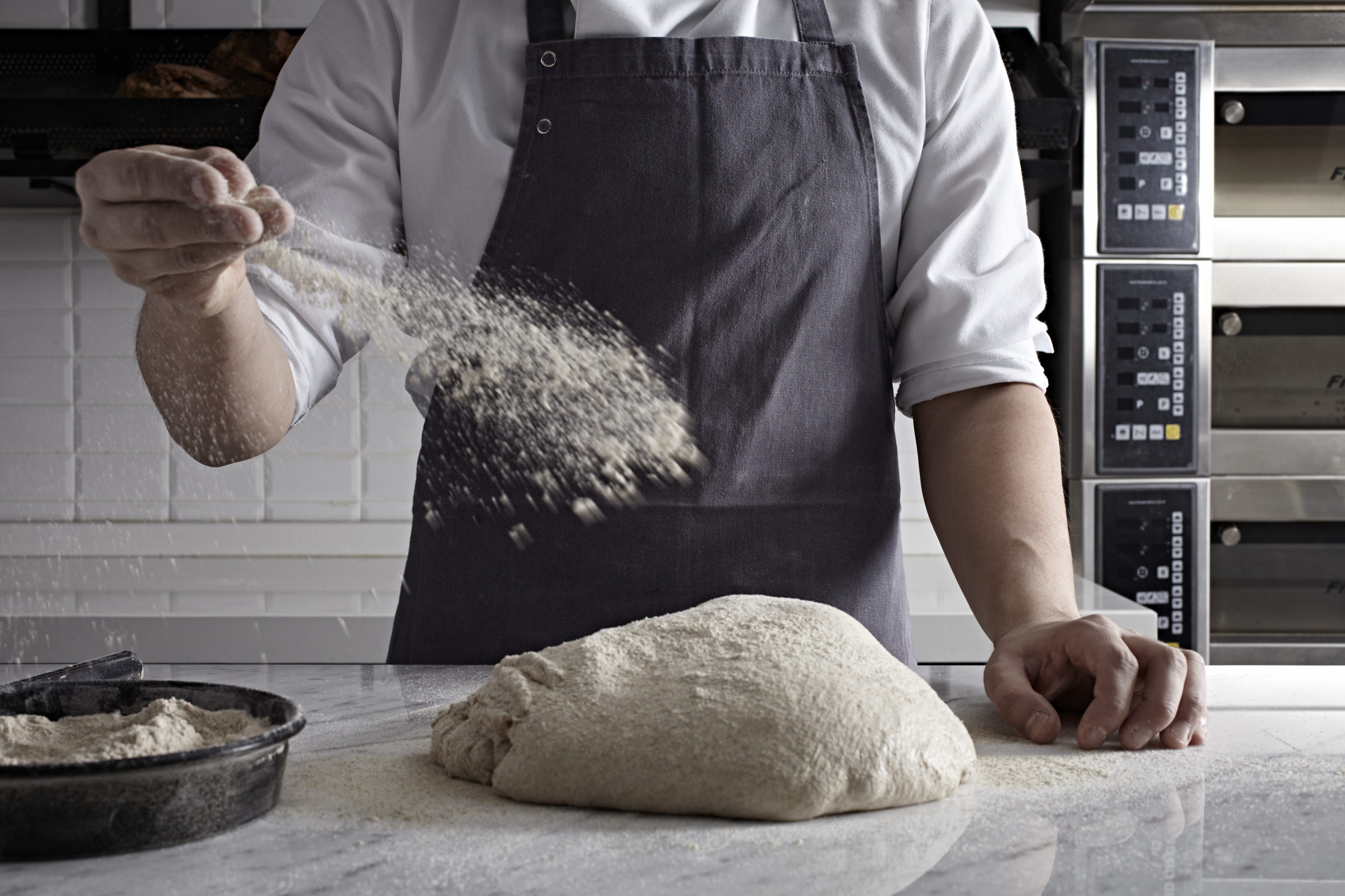 A man dusting flour on bread dough.