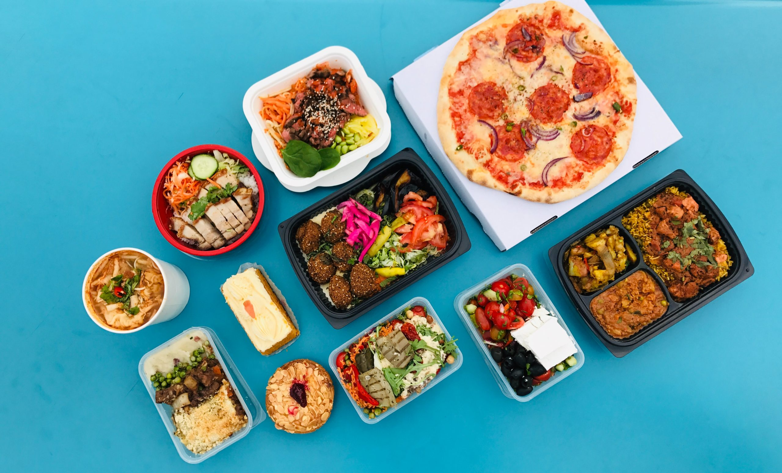An assortment of prepared meal kits on a blue table.