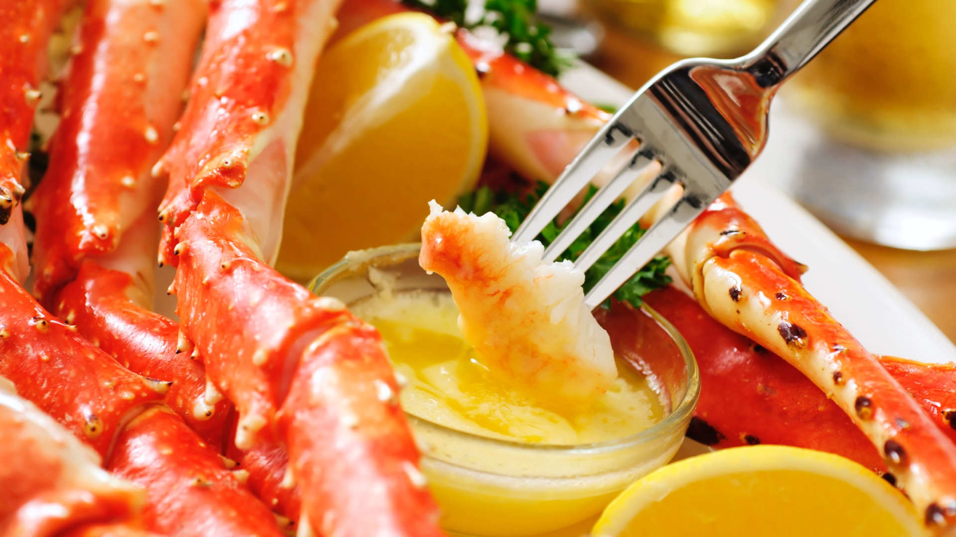A fork with a piece of crab dipping into melted butter.