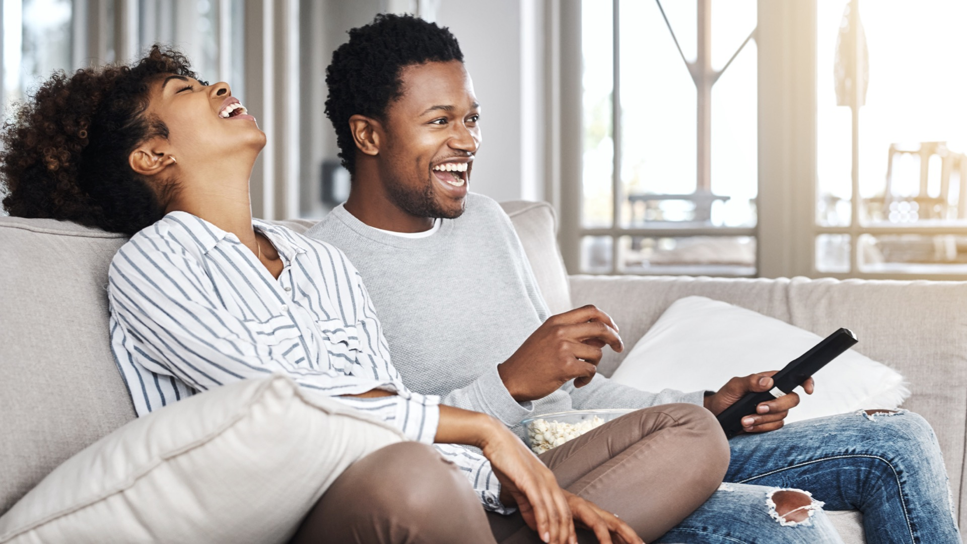 A couple sitting on a couch watching a movie.