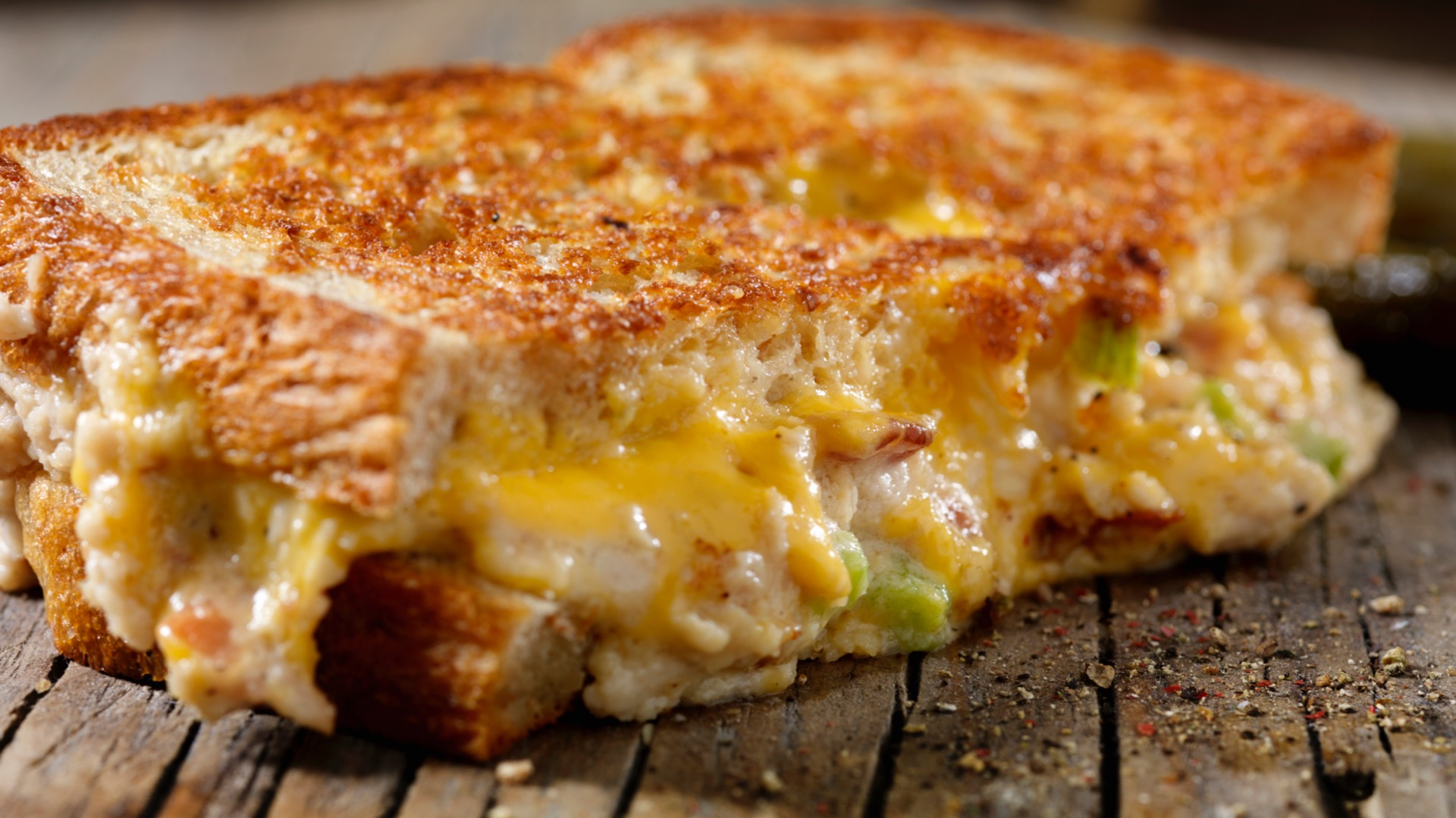 Half of a grilled cheese sandwich on table - best grilled cheese recipes in Batlimore