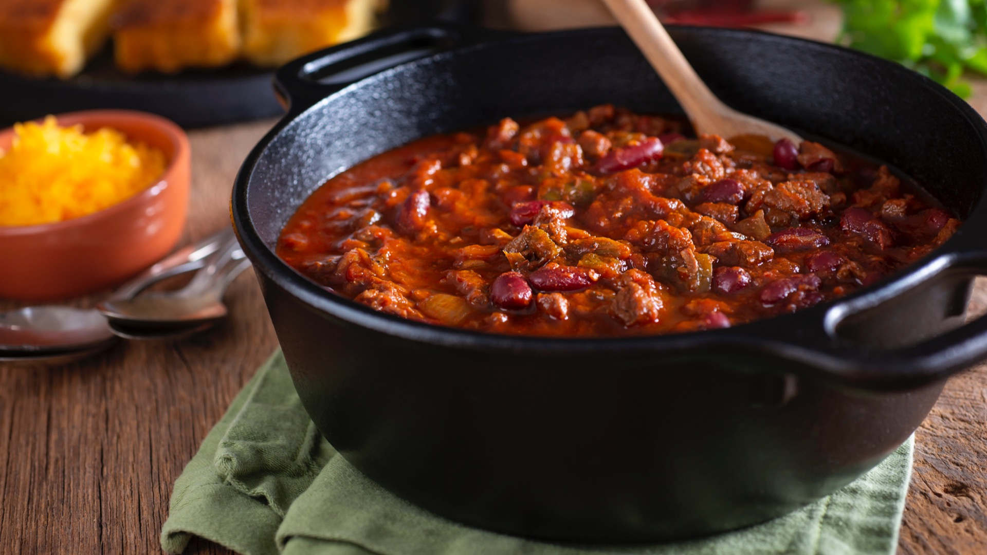A pot of chili on a green towel with a wooden spoon in the pot | chili in Baltimore